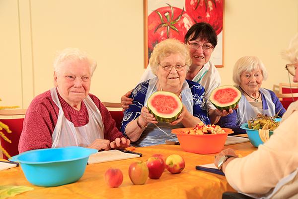 Senioren am Tisch bereiten Obst vor
