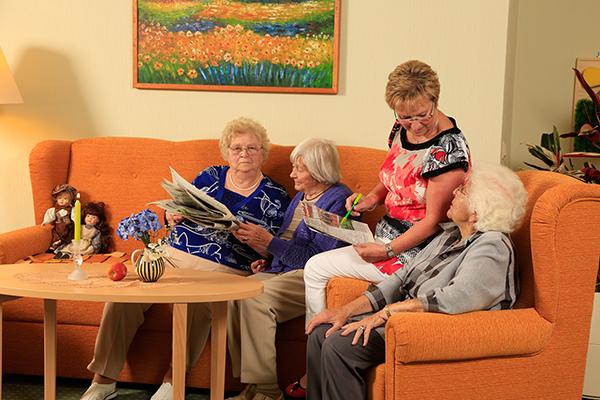 Seniorinnen mit Betreuungskraft am Tisch bei der Zeitungsschau