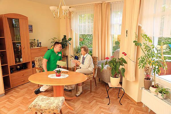 Seniorin mit Pfleger am Tisch