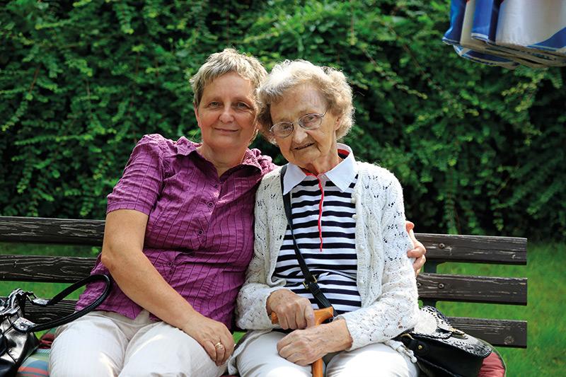 Seniorin auf Bank im Garten