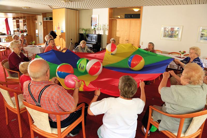Senioren im Stuhlkreis mit Schwungtuch